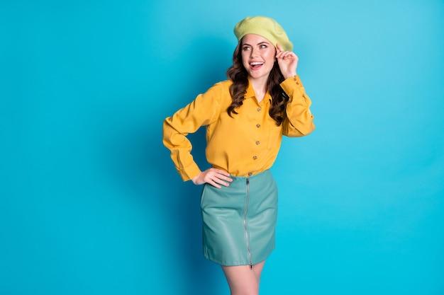 La foto di una ragazza adorabile e candida si gode le vacanze di primavera, guarda il copyspace, tocca il berretto, vuoi attirare il ragazzo, indossa vestiti di bell'aspetto isolati su uno sfondo di colore blu