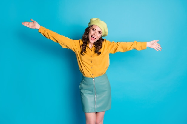 La foto di una ragazza candida e adorabile con le mani aperte vuole abbracciare la sua amica isolata su uno sfondo di colore blu