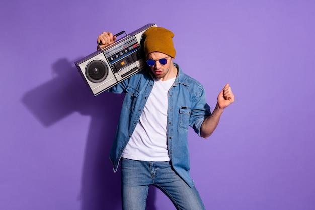 Foto del ragazzo alla moda funky rilassante spensierato che tiene il suono del registratore con la sua mano che balla divertendosi isolato sopra priorità bassa di colore vivido viola
