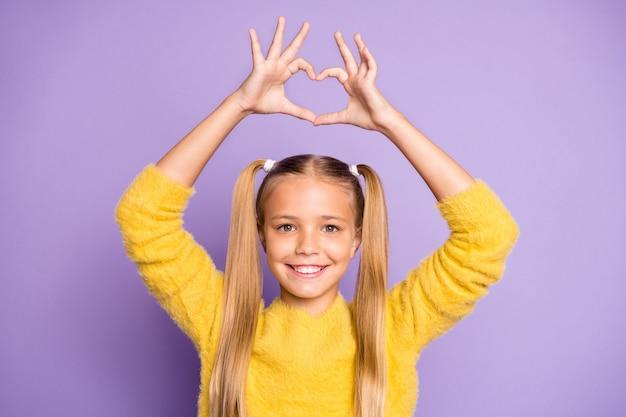 La foto della ragazza divertente sveglia allegra casuale che mostra il segno di forma del cuore con le dita sopra la sua parete viola pastello della testa ha isolato