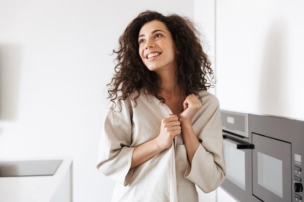 Foto di donna riccia caucasica con lunghi capelli scuri che indossa abiti di seta per il tempo libero sorridendo e guardando da parte mentre si trova in cucina vicino al luogo di cottura