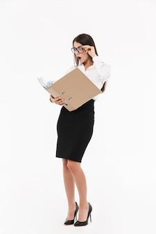 Foto di una donna d'affari caucasica lavoratrice vestita con abiti formali che tiene in mano un rilegatore con documenti mentre lavora in ufficio isolato su un muro bianco