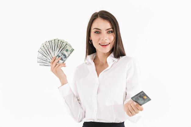 Foto di una donna d'affari caucasica lavoratrice vestita con abiti formali che tiene denaro contante e carta di credito mentre lavora in ufficio isolato su un muro bianco