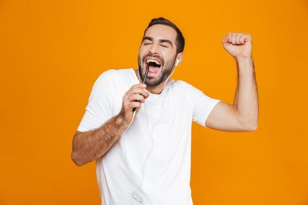 Foto dell'uomo caucasico 30s che canta mentre si utilizzano gli auricolari e il telefono cellulare, isolato