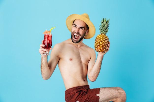 Foto di un turista caucasico senza camicia che indossa un cappello di paglia che sorride mentre tiene in mano ananas e cocktail isolati