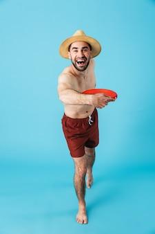Foto di un turista caucasico senza camicia che indossa un cappello di paglia che sorride mentre lancia e gioca a frisbee da spiaggia isolato su blu