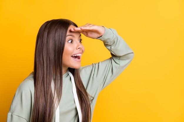 Foto di una bambina adorabile e adorabile vestita con un vestito verde casual che guarda lontano spazio vuoto braccio fronte isolato colore giallo sfondo