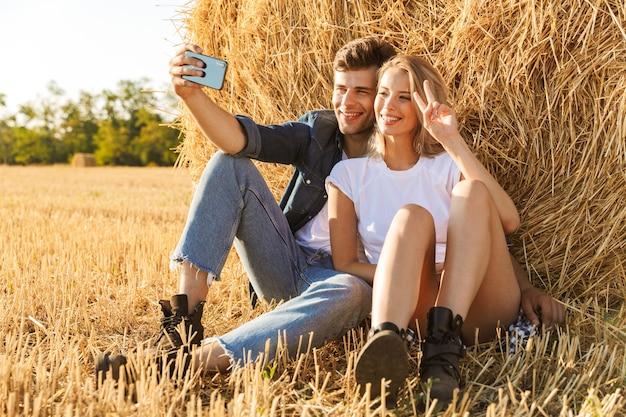 Foto di affascinante coppia uomo e donna che prendono selfie seduti sotto un grande pagliaio in campo dorato, durante la giornata di sole