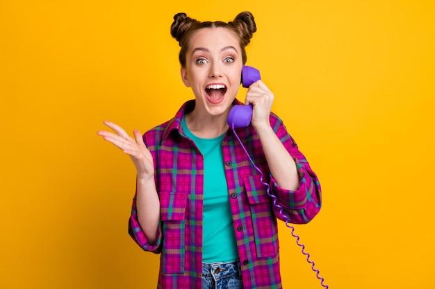 Foto di affascinante signora pazza funky due panini divertenti tenere cavo telefono cornetta parlare amici ascoltare pettegolezzi freschi chiacchiere chiacchiere indossare camicia a quadri casual isolato colore giallo sfondo