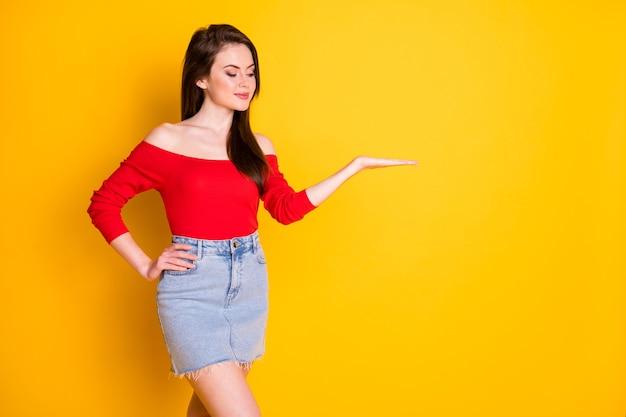 Foto di affascinante giovane ragazza carina braccio lato anca palmo tenere guardare spazio vuoto negozio centro commerciale vendite prodotto indossare camicia spalle scoperte denim minigonna isolato vibrante colore giallo sfondo