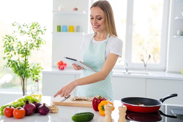 La foto dell'affascinante casalinga gode del fine settimana di mattina cucinando tenendo il libro elettronico che controlla la ricetta che dirige la cipolla in linea del dito del cuoco in linea cucina bianca all'interno