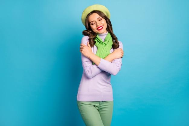La foto dell'affascinante signora con gli occhi chiusi che si abbraccia si gode l'armonia interiore indossa il berretto verde, il maglione viola, la sciarpa, i pantaloni, la parete di colore blu