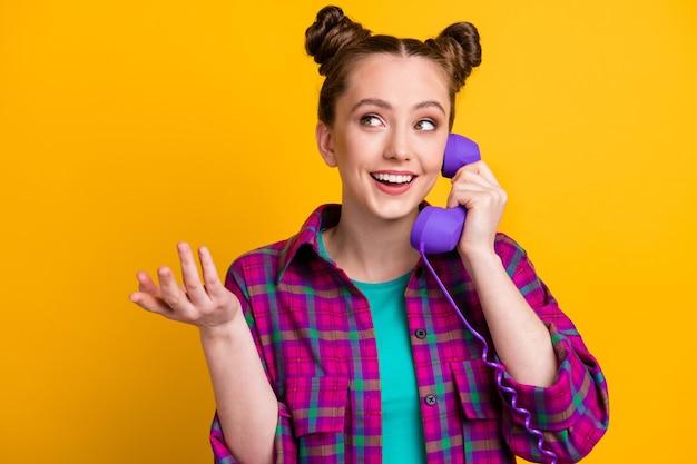 Foto di una signora affascinante due panini divertenti tengono la cornetta del telefono via cavo parlando in chat amici che discutono di pettegolezzi freschi le voci indossano una camicia a quadri casual isolata colore giallo brillante sfondo