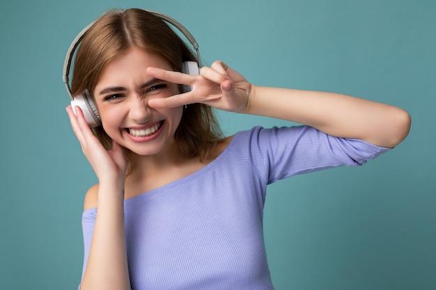 Foto di affascinante giovane donna bionda sexy sorridente che indossa un top corto blu isolato su sfondo blu