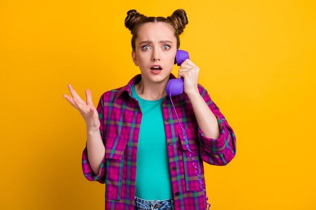 Foto di un'affascinante signora terrorizzata due panini divertenti tenere il cavo del telefono cellulare parlare capo che rimprovera il suo errore commesso progetto indossare una camicia a quadri casual isolato sfondo di colore giallo
