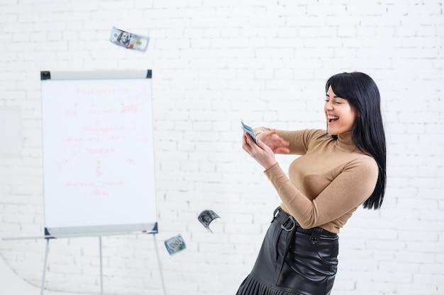 Foto di una donna affascinante con un sorriso che tiene dei soldi in mano e li lancia in aria