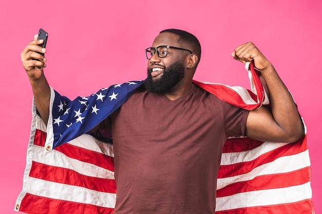 Foto di allegro americano africano uomo manifestante sollevare bandiera nazionale americana i neri rivoluzione amore tutti gli esseri umani esprimono solidarietà unità isolato su sfondo rosa. utilizzo del telefono cellulare.