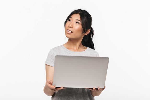 Foto di bella giovane donna asiatica allegra che posa isolata sopra la parete bianca facendo uso del computer portatile.