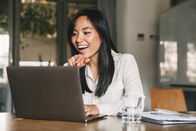 Foto di donna asiatica allegra 20s indossa una camicia bianca ridendo e puntando il dito sullo schermo del computer portatile, mentre parla o chiacchiera in videochiamata in ufficio