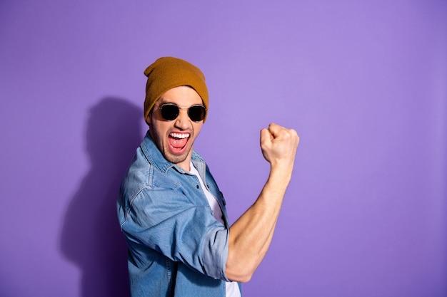 Foto di allegro attraente bell'uomo pazzo che ti mostra i suoi muscoli bicipiti urlando con la vittoria che indossa il berretto copricapo isolato su sfondo di colore vivido viola