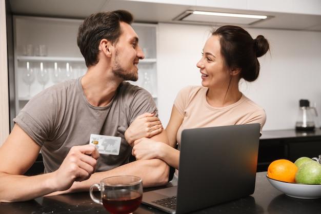 Foto di coppia allegra uomo e donna che utilizza computer portatile con carta di credito, mentre era seduto in cucina