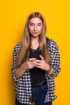 Foto di allegra carina bella giovane donna in chat dal telefono cellulare isolato sopra la parete gialla della parete. guardando da parte.