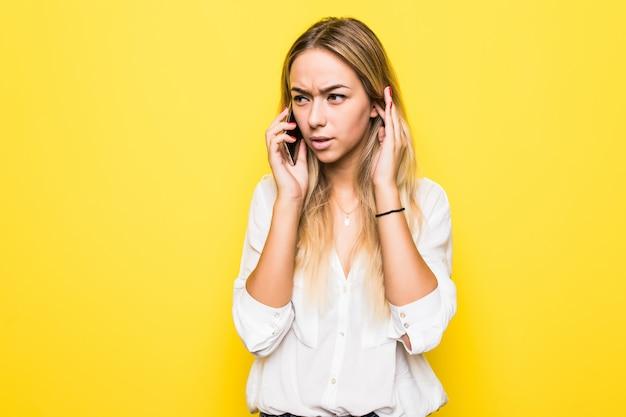 Foto di allegro carino bella giovane donna parla al telefono cellulare isolato sopra il muro giallo muro.