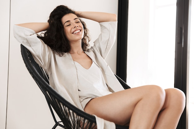 Foto di donna allegra carina con lunghi capelli scuri che indossa abiti di seta per il tempo libero sorridente, con gli occhi chiusi mentre era seduto in poltrona in un accogliente appartamento