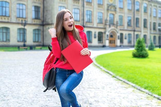 Foto di una persona allegra e divertente, attiva, eccitata, hipster, che tiene in mano un testo con una promozione che ottiene