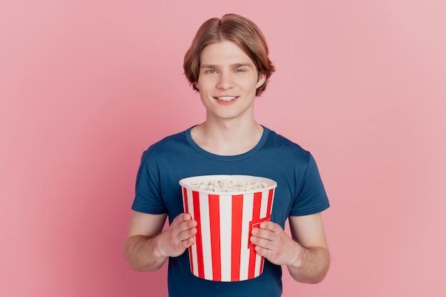 Foto di un ragazzo allegro che tiene una scatola di carta per popcorn felice sorriso positivo guarda il cinema isolato sfondo di colore rosa