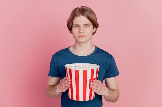 Foto di un ragazzo allegro che tiene in mano una scatola di carta per popcorn, un sorriso positivo e felice, che guarda un film tv isolato sfondo di colore rosa