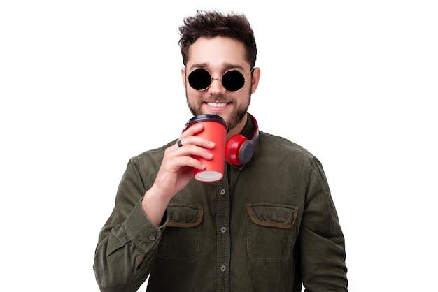 Foto di un ragazzo allegro, con occhiali da sole e cuffie, con in mano una tazza di caffè su un muro di pentecoste
