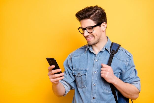 Foto dell'uomo attraente bello allegro che passa in rassegna attraverso il telefono che sorride a trentadue denti con lo zaino dietro la parete di colore vivida isolata in jeans denim