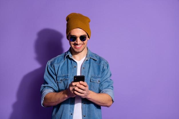 Foto di allegro gentile blogger amichevole tenendo il telefono con le mani poting notizie nei feed dei social media sorridente a trentadue denti indossando giacca di jeans isolato su sfondo di colore vivido viola