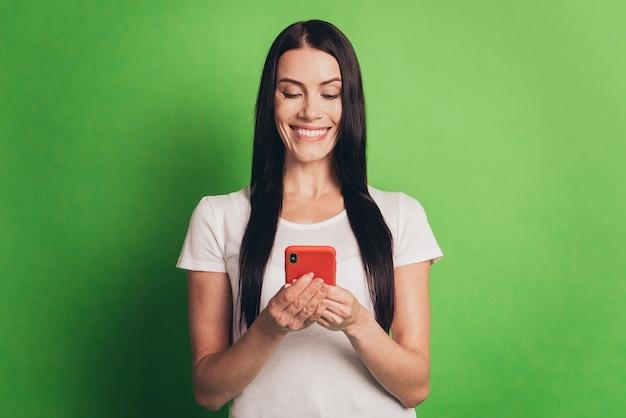 Foto di una signora allegra con il telefono che legge notizie online isolato sfondo verde