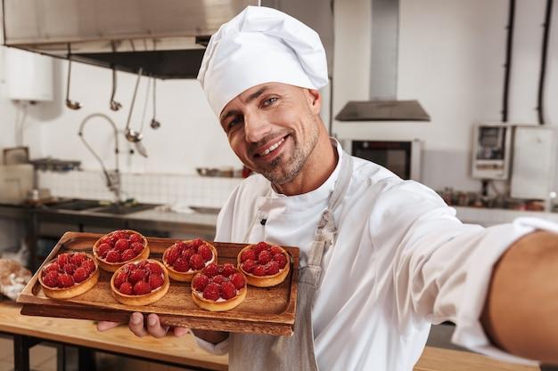 Foto del capo maschio allegro in uniforme bianca che prende selfie e che tiene il piatto con le torte