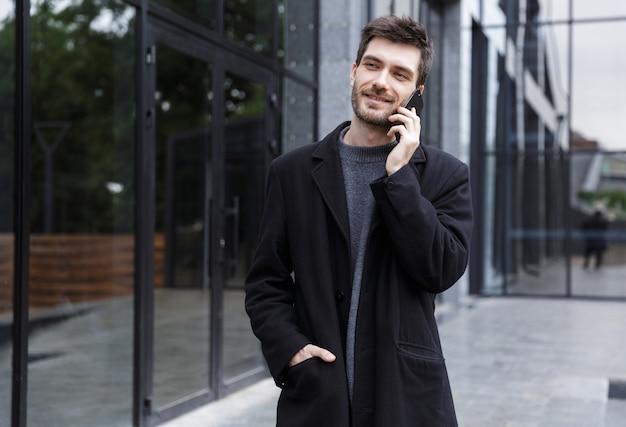 Foto di allegro uomo 20s parlando al cellulare, mentre si cammina all'aperto vicino a un edificio di vetro