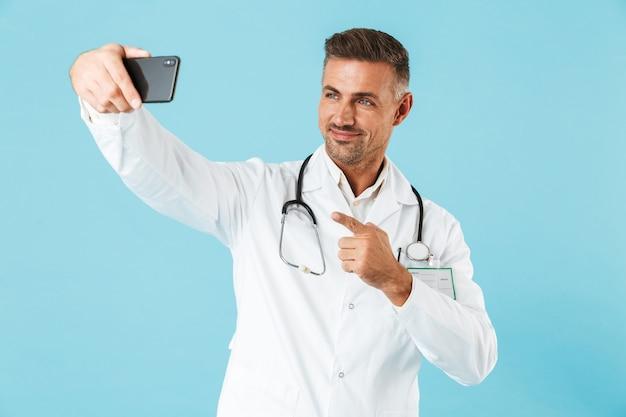 Foto di allegro medico che indossa camice bianco e stetoscopio prendendo selfie sul cellulare, in piedi isolato sopra la parete blu