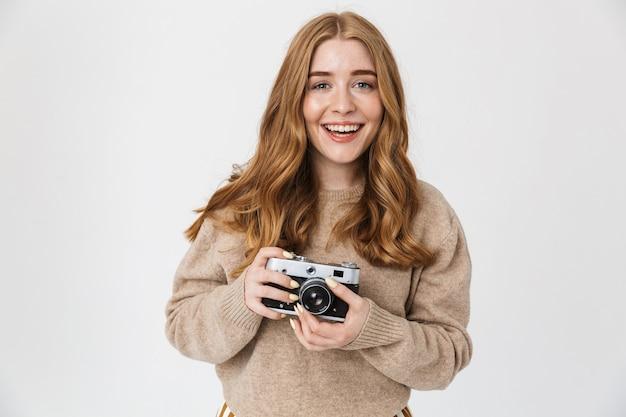 Foto di un allegro contento carino giovane ragazza adolescente in posa isolato su muro bianco muro tenendo la fotocamera fotografare.