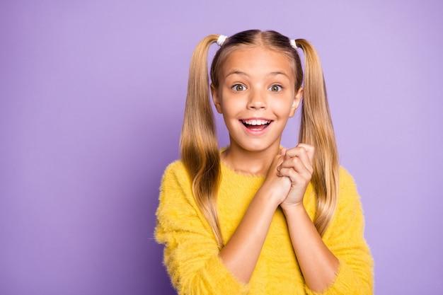 Foto di ragazza carina positiva allegra che esprime emozioni positive sul viso sorridente a trentadue denti con le mani piegate parete di colore viola pastello isolato