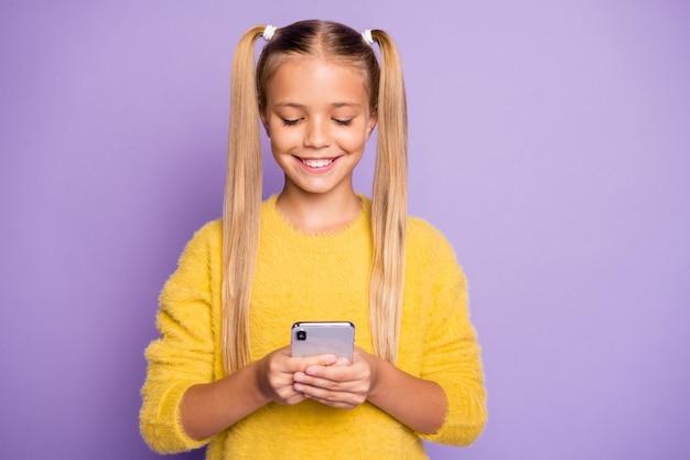 Foto della ragazza carina positiva allegra che sorride toothily sfogliando il telefono isolato sopra la parete viola di colore pastello