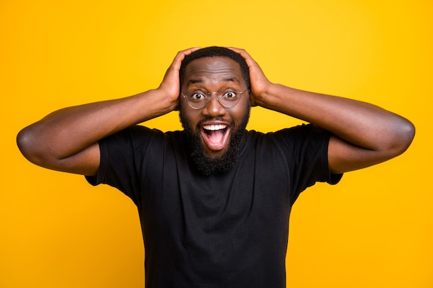 Foto di allegro positivo divertente carino uomo nero felicissimo per il centro commerciale scontato afferrando la sua testa con le mani in t-shirt isolato colore vibrante parete gialla