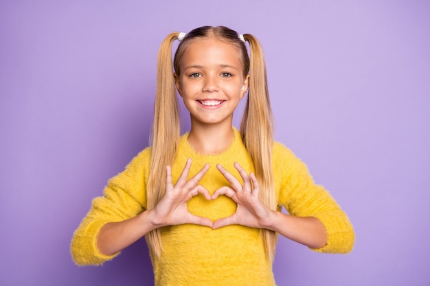 La foto della ragazza positiva allegra che sorride alla moda alla moda che mostra il segno di forma del cuore con le dita ha isolato la parete di colore viola pastello