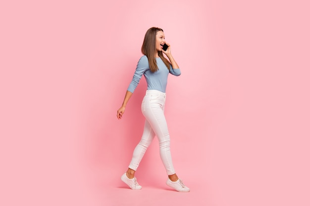 Foto di allegra ragazza positiva parlando con i suoi amici sul telefono in scarpe da ginnastica bianche isolate in movimento su sfondo di colore pastello