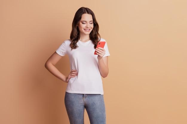Foto di una donna allegra e positiva che tiene il telefono leggendo il post sul blog in posa su sfondo beige