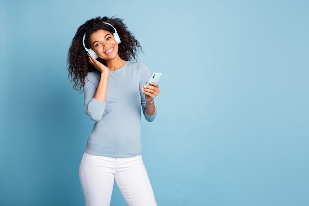 Foto di allegro positivo bella ragazza piuttosto dolce sorridente a trentadue denti godendo il suono dei suoi nuovi auricolari tenendo il telefono in pantaloni bianchi isolato blu pastello colore di sfondo