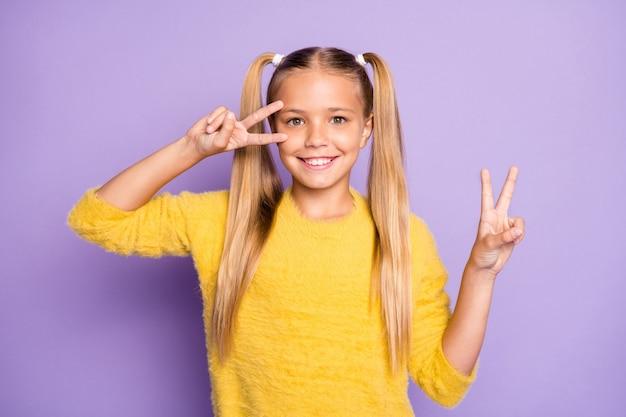 Foto di allegro preadolescente positivo che ti mostra il doppio segno di v nel muro di colore viola pastello isolato di buon umore