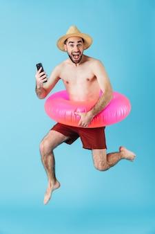 Foto di un allegro turista a torso nudo che indossa un anello di gomma che sorride e tiene il cellulare isolato sopra il blu