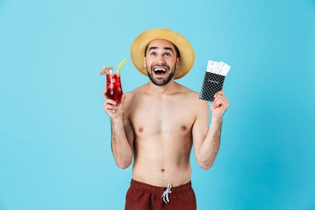 Foto di un allegro turista a torso nudo che indossa un cappello di paglia che sorride mentre tiene in mano cocktail e biglietti di viaggio con passaporto isolato