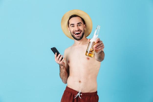 Foto di un allegro turista a torso nudo che indossa un cappello di paglia che sorride mentre tiene in mano uno smartphone e una bottiglia di birra isolati sopra il blu